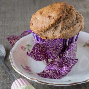 Muffin végane dans une caissette en papier rayé blanc et violet posé sur une assiette