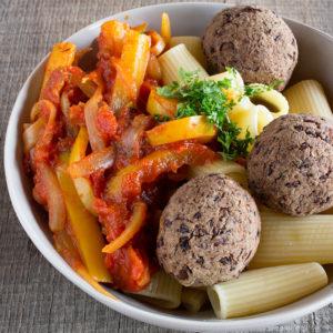 Assiette de pâtes sauce tomate et poivron avec boulettes de haricots noirs