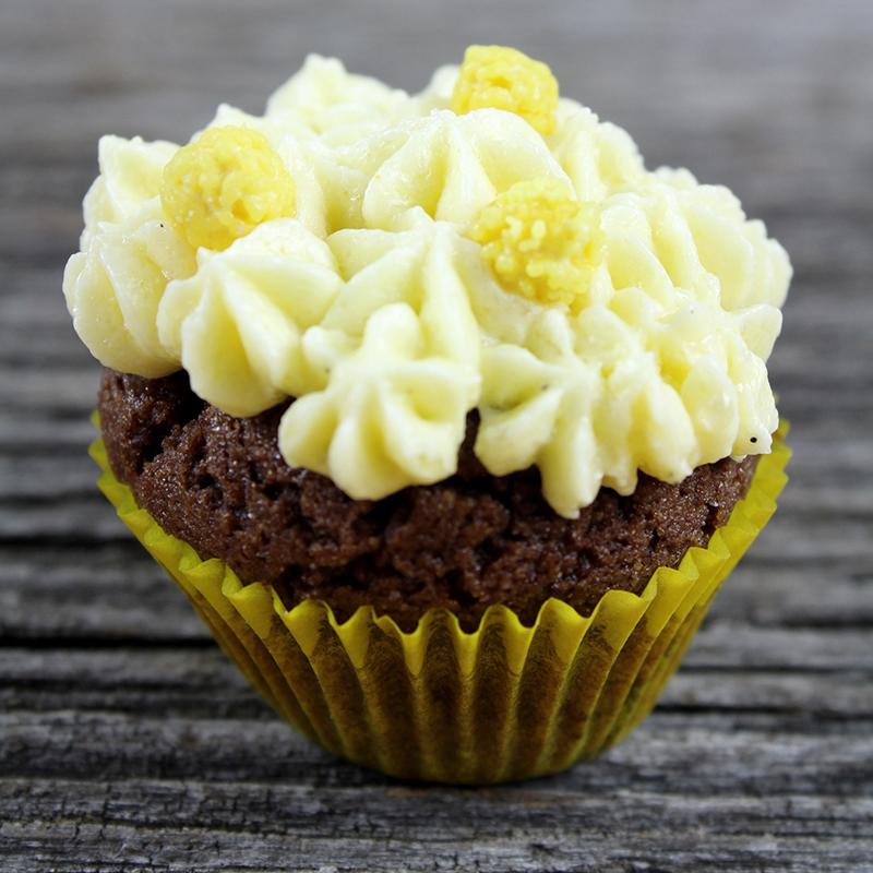 Cupcake chocolat vanille dans caissette jaune sur fond de bois gris