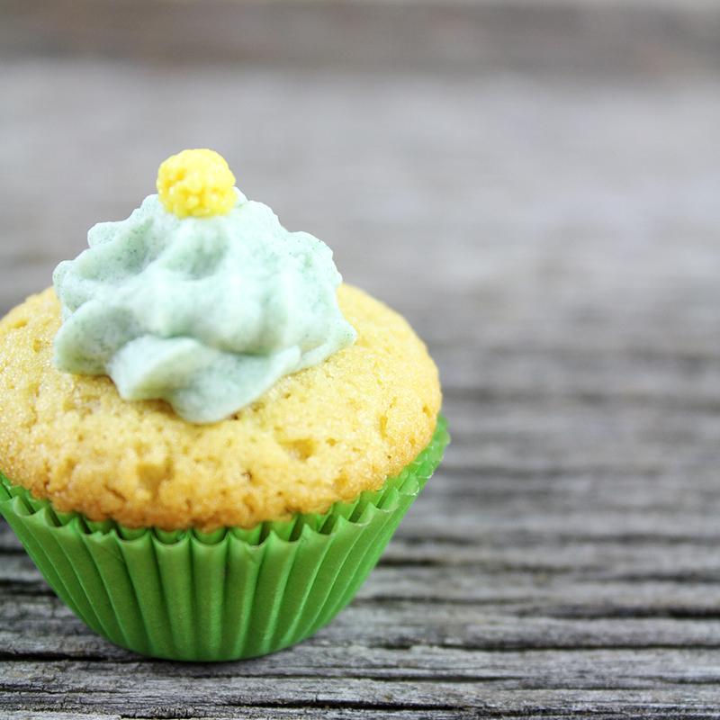 Cupcake au citron dans caissette verte sur fond de bois gris