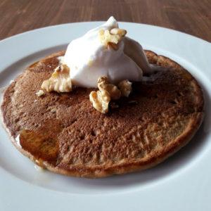 Pancakes véganes avec chantilly de coco, noix sur assiette blanche