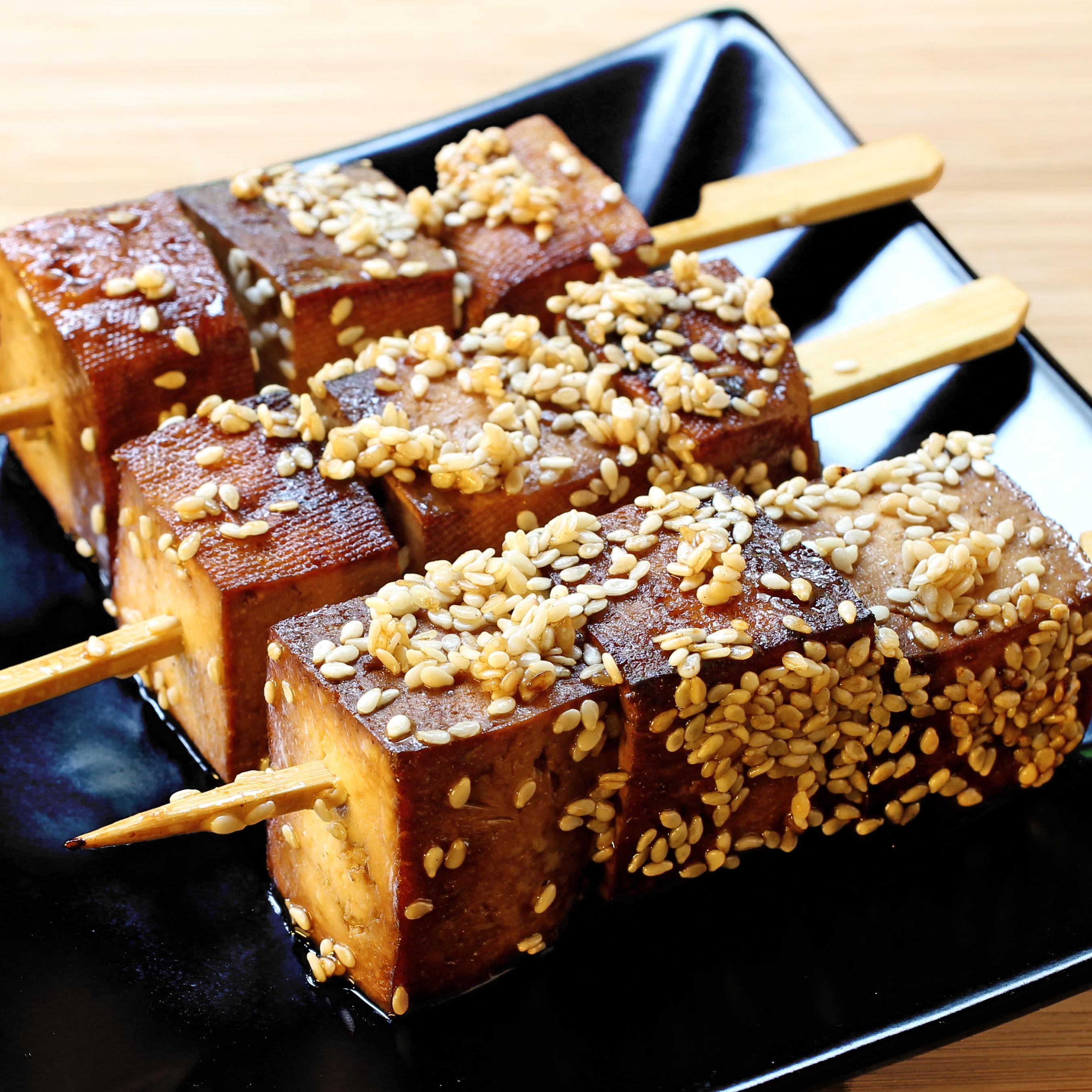 Brochettes de tofu au sésame sur assiette carrée noire