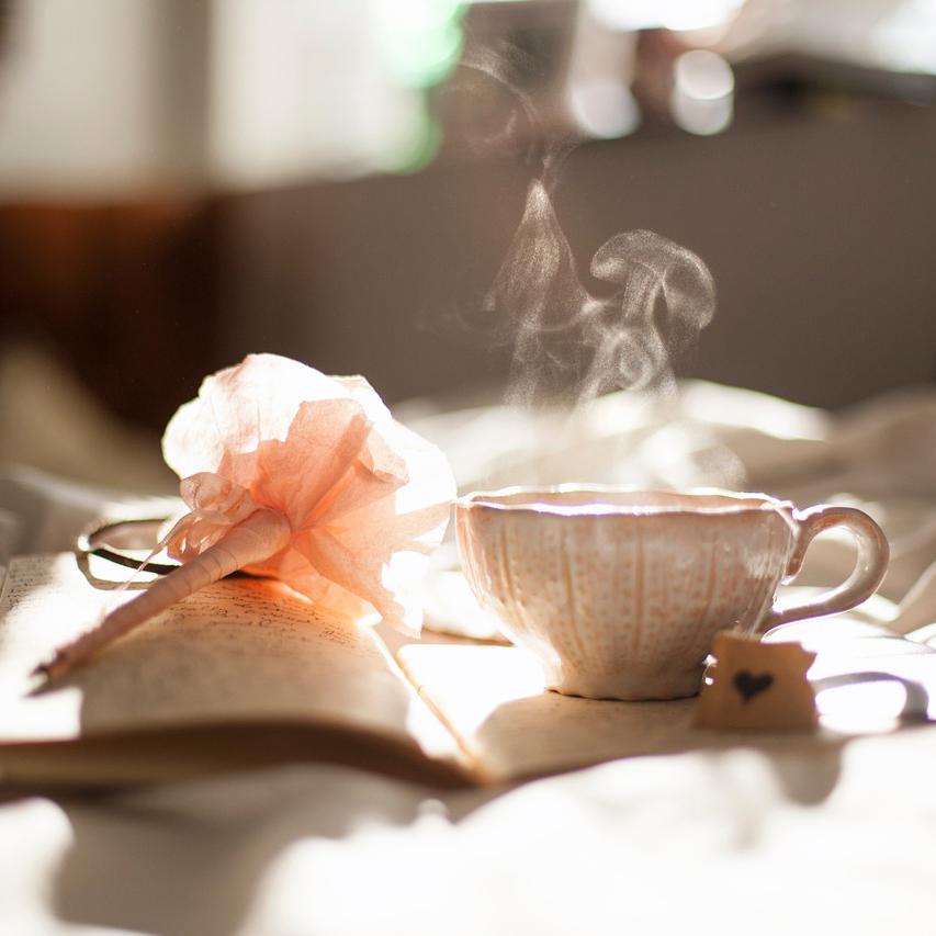 Tasse de thé fumant et livre ouvert