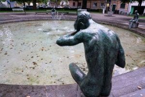Fontaine vide avec personnage en bronze