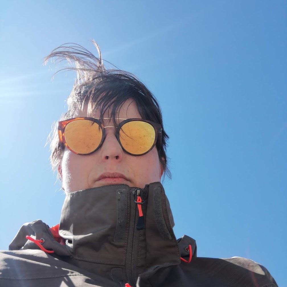 Loetitia Monge avec lunettes de soleil sur fond de ciel bleu
